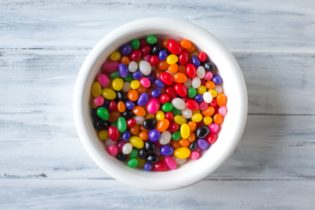 A picture of a bowl with jelly beans on a marble background.