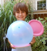 A picture of a kid holidng a balloon and a paddle. Getting ready to play balloon badmitten.