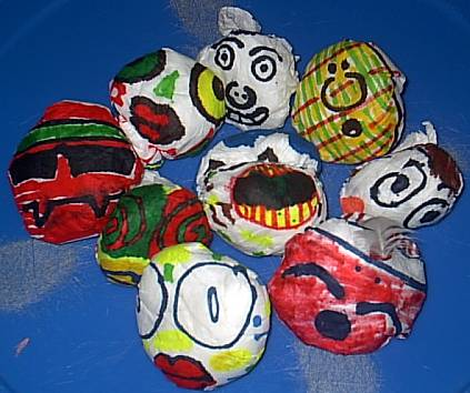 A picture of about 10 homemade bean bags. The bags have different designs including some faces drawn on them.