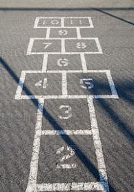 An image of hopscotch drawn on black pavement.
