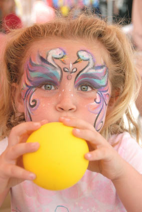 An image of a girl blowing up a yellow balloon. She has swans painted above her eyes with decorative designs painted down her cheeks.
