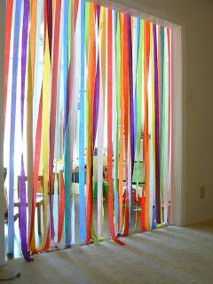 An image of crepe paper strung from the top of a doorway and just touching the floor. Various colors. Everybody walking through this door way would have to go through crepe streamers.