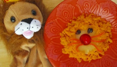 An image of a stuffed lion next to a bowl with a lion face made out of pineapple as the head, carrot as the hair, raisins as the eyes, cherry as the nose, and strings of carrot as the whiskers.