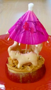 An image of an apple sliced horizontally with three animal crackers and an umbrella on top making it look like a carousel.
