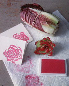 A picture of bunched cabbage, red ink, and paper with cabbage ink stamps. Showing how you can use the fruits and vegetables to create beautiful art.