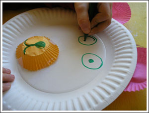 A picture of a child making a teddy bear face on a paper plate. Using green marker to make the eyes and a cupcake liner for the nose.