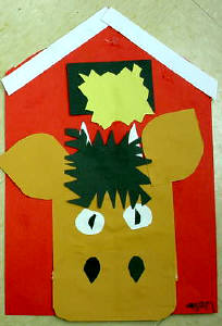 A picture of a cow and barn craft. Shows a cows head pasted to a red barn.