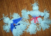 A picture of two yarn doll crafts with a wooden background.