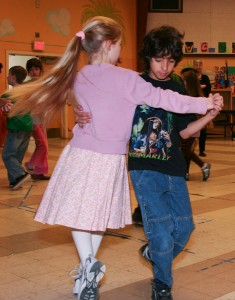 A picture of a young girl and boy line dancing.