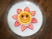 A picture of a pancake with a smiley face made out of fruit. There's cut up strawberries laid out around the pancake to represent the suns rays.