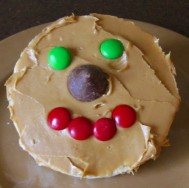 A rice cake with peanut butter spread on top. A hershey's kiss in place of it's nose, red M&Ms as the mouth, and green M&Ms as the eyes.