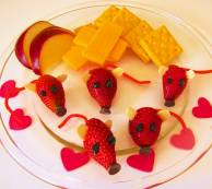 A picture of strawberries decorated as a mouse with crackers and apples.