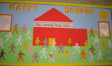 A bulletin board with a red school on it with words that say Happy School. there are sever kids either painted or drawn around the red school.