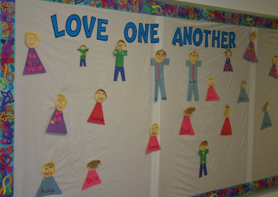 "A bulletin board with images of different boys and girls on the board. It appears as if they were crafted out of construction paper and glued to the board. The heading of the bulletin board is ""Love One Another."""