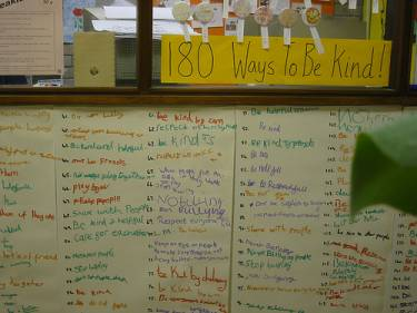 "A white board with a list of different ways to be kind written on it. The heading of the whiteboard reads ""180 Ways to Be Kind."""