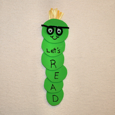 "A picture of a bookmark book worm. Several green circles stacked on top of each that says ""let's read."" The worm has googly eyes and glasses as well."
