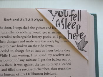 "A picture of a corner bookmark with words that say ""you fell asleep here."""