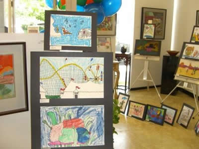 A picture of an art show as a school event. Different kids drawing and art work displayed in the room.