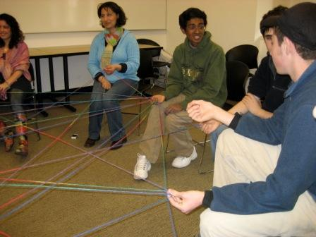 A picture of people sitting in a circle playing the spiderweb of friendship get to know you game.