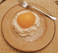 A picture of a peach half on whipped cream with a fork laying next to it. It looks like an over-easy egg.