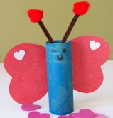 A picture of a butterfly craft made from a toilet paper tube, painted blue, and the wings are cut in the shapes of hearts from red construction paper.