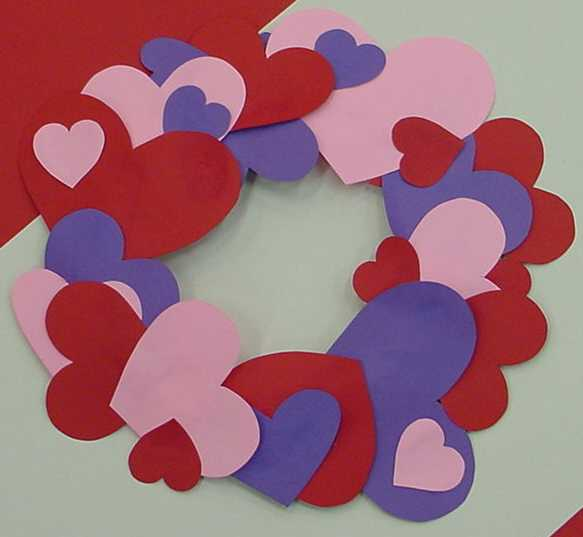 A picture of a heart wreath made from construction paper heart cutouts. The colors are red, pink, and blue. The hearts are small, medium, and large forming a large wreath.