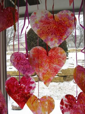 A picture of hearts dangling from red ribbon. The hearts are various colors and have a unique pattern to them.