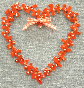 A heart formed from puzzle pieces with a ribbon on the heart.