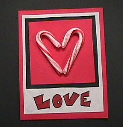 """Two candy canes used to form a heart on a card that says """"love""""."""