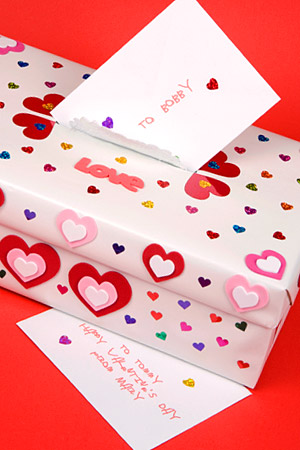 A shoe box decorated in small and medium colorful hearts. There is an opening to put valentines cards in and the picture shows a card being dropped into the opening.