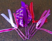 A picture of decorative paperclip bookmarks. The paperclips have lacy, pink, red, and purple strands coming from the paperclip.