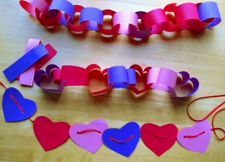 A picture of valentines construction paper chains. One has heart shapes. One has circular shapes. The other is just a string of heart cutouts. All in blue, purple, pink, and red construction paper colors.