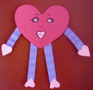 A heart cut from red construction paper with a feminine face on it. The arms are made from purple accordion construction paper and the hands and feet are made from pink heart construction paper cutouts.