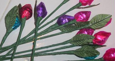 An image of green stems and leaves with a Hershey's kiss attached to them making it look like a rose.