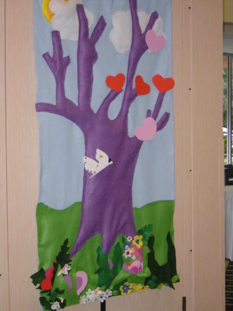An image of art. The tree is purple, the leaves are red and pink hearts. There's grass and flowers around the base of the tree.