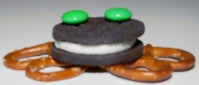 An Oreo with pretzels and green M&M's assembled to look like a frog.