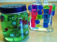 An image of two jars filled with gel and objects to make a cool decorative piece.