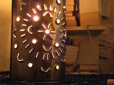 A tin can with a decorative pattern made from different holes or slots. The holes and slots allow light to illuminate from the candle on the inside of the can.