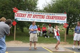 "A picture of two people competing in a cherry pit spitting contest with people looking on. The sign in the background reads ""Cherry Pit Spitting Championship."""