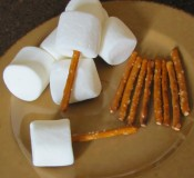 A picture of marshmallows and pretzel sticks on a plate.
