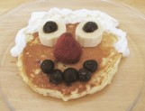 A picture of a pancake smiley face. Fruit making the nose, mouth, and eyes, and whipped cream as the hair.