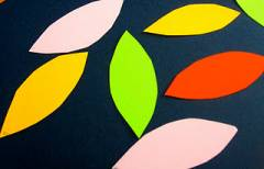 An image of construction paper leaf cutouts. Pink, green, red, and yellow.