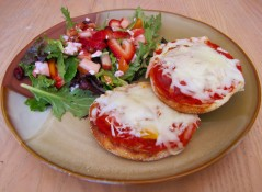 A picture of pizza made on a bagel with a salad sitting next to them.