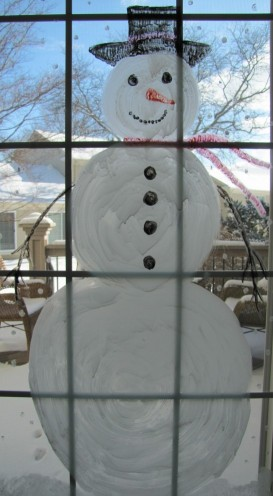 A picture of a large snowman painted on a window.
