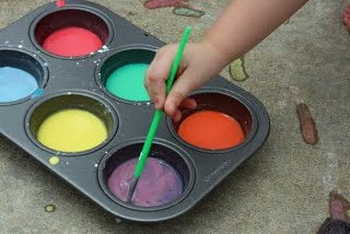 A picture of a muffin pan filled with different colored paint. A child's hand is dipping a paintbrush into the purple paint.