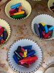 A picture of broken pieces of crayon in a muffin pan liner.