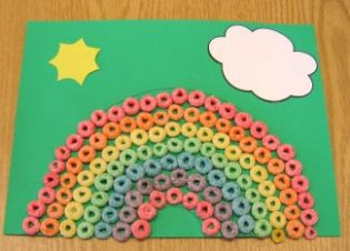 A picture of a fruit loops rainbow on green construction paper with a sun and cloud.