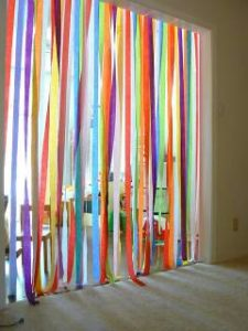 A picture of a doorway decorated with different colored streamers. You have to walk through the rainbow colored streamers to transition from room to room.