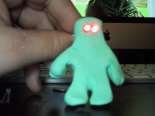 A picture of gumby made out of clay with red eyes.