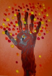 A arm and hand print on construction paper. The arm looks like the trunk of the tree and the fingers are the branches. Orange, yellow, and red paint dots for leaves.